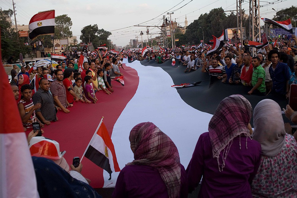 On July 1: Protesters come together to wave a giant Egyptian flag.