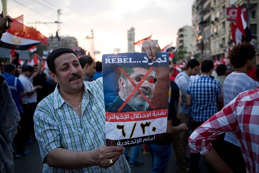 July 1: An opposition supporter holds a picture of President Morsi with missing eyes, outside the presidential palace.