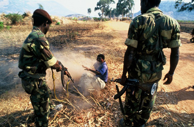 A young man is shot by the MPLA soldiers during Angola's longest running civil war. The MPLA were applying forceful conscription on the village people. The man being strafed by the AK-47 had rejected the ides of joining the MPLA.