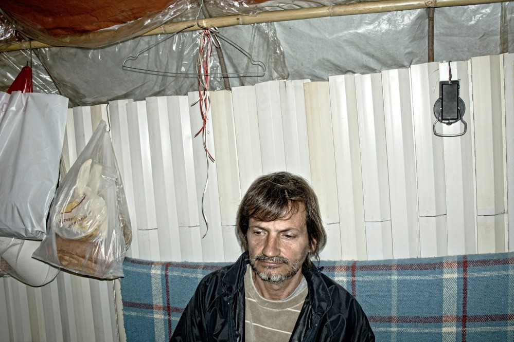 The old shutters became a wall, carboard boxes turned into a sofa, and pieces of nylon make up the curtains; this is Nikos' makeshift house. He used to be a contract employee of the broader public sector and lived in the northern suburbs of Athens. He now lives on a hill near the beach, about 100 yards from the waves.