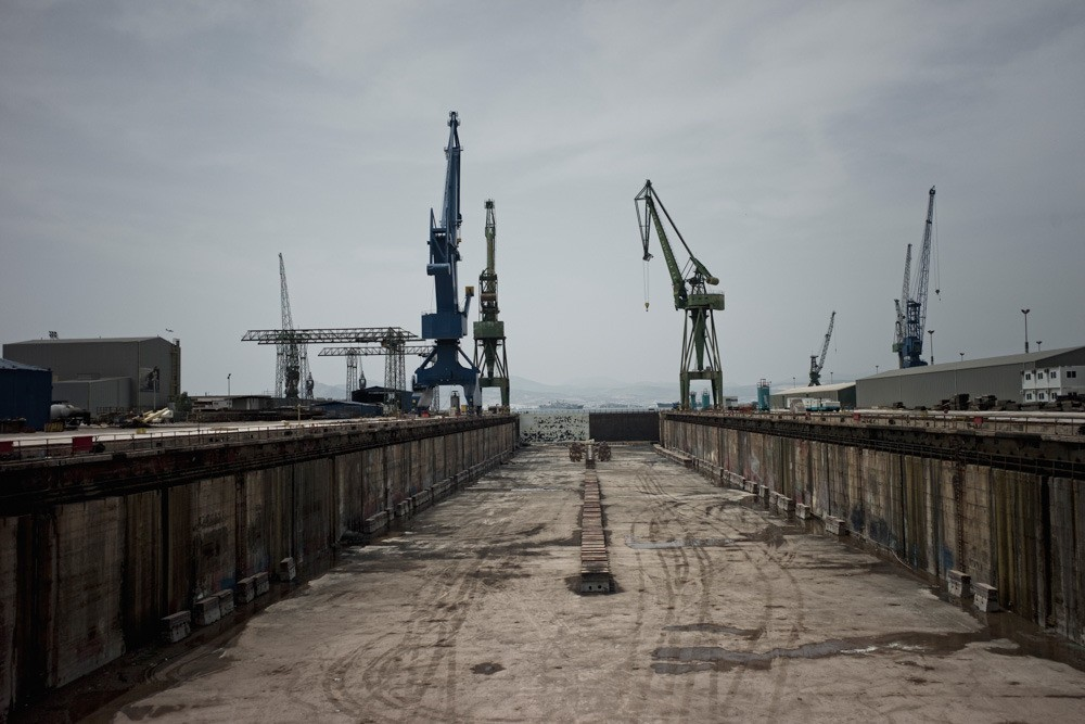 """Six thousand workers used to work here in the Scaramaga shipyard. It has been termed the """"sick man"""" of the Greek Economy, after a series of transactions between Greek governments and foreign investors. Hundreds of articles have been written on scandals and malfunctioning submarines that tilted to one side. In October 2013, the shipyard officially stopped working with the 1100 remaining workers being practically thrown on the street."""