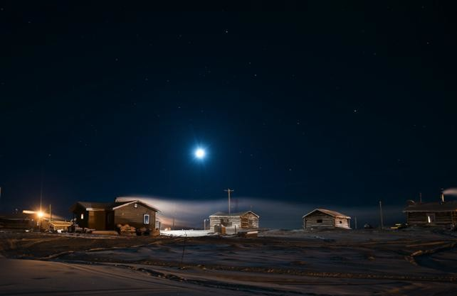 A nighttime view of log homes and trapper cabins in Colviille Lake, NWT.