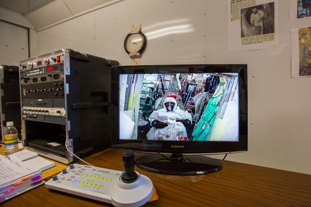 Ένας εργάτης στην εγκατάσταση Hanford, διακρίνεται σε τηλεοπτικό μόνιτορ να φοράει μια προστατευτική στολή επιπέδου Β, καθώς καθαρίζει το πιο επικίνδυνο δωμάτιο της εγκατάστασης, το Plutonium Finishing Plant's Americium Recovery Facility, γνωστό και ως McCluskey Room. Το όνομα αυτό το πήρα από τον πρώην εργάτη της εγκατάστασης Harold McCluskey, ο οποίο τραυματίστηκε το 1976, όταν μετά από ένα ατύχημα, τόσο αυτός όσο και όλο το δωμάτιο εκτέθηκαν στην ακτινοβολία ραδιενεργού υλικού.