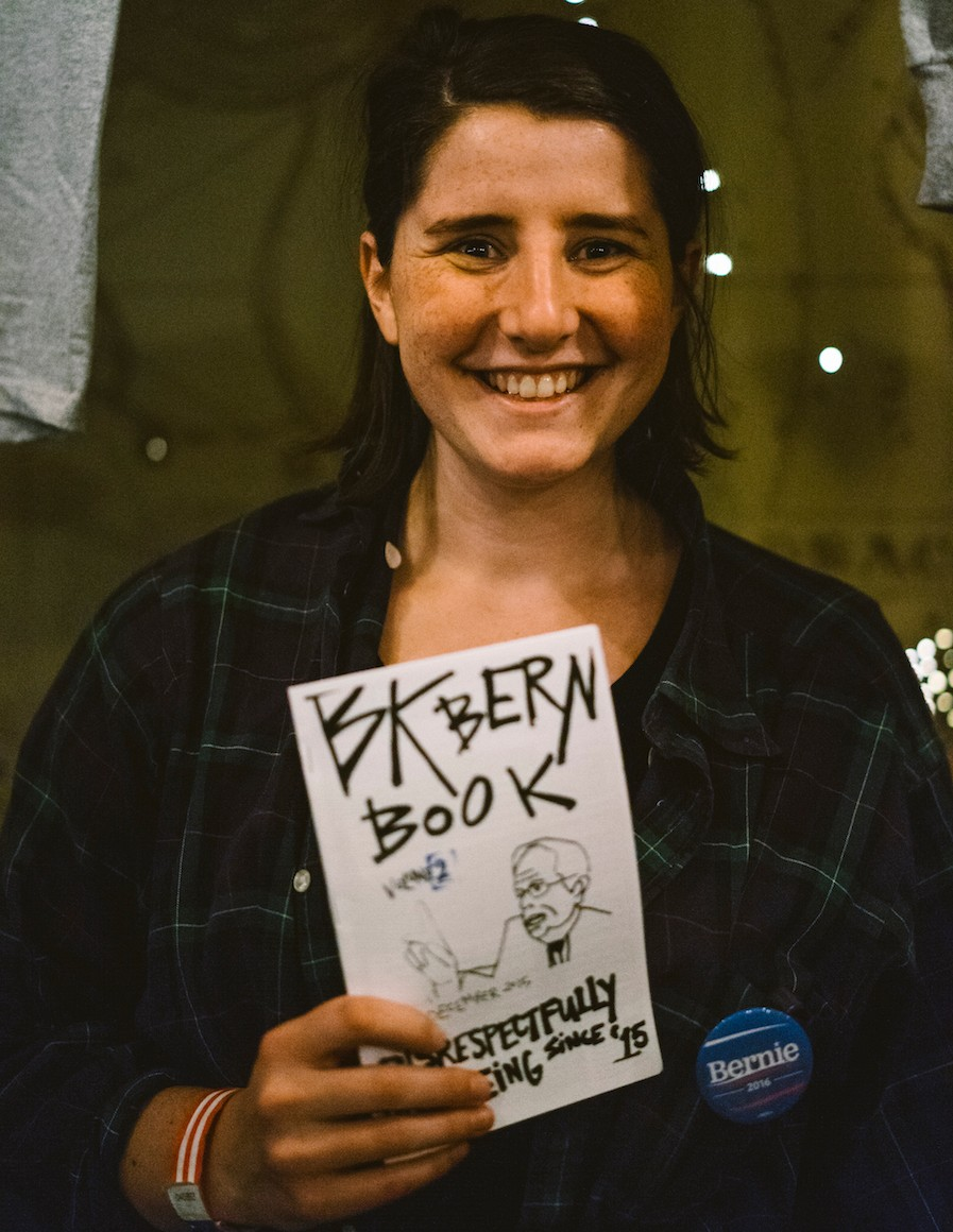 Volunteer Lauren Irwin holds the second issue of her Sanders' fanzine 'BK Bern Book.'