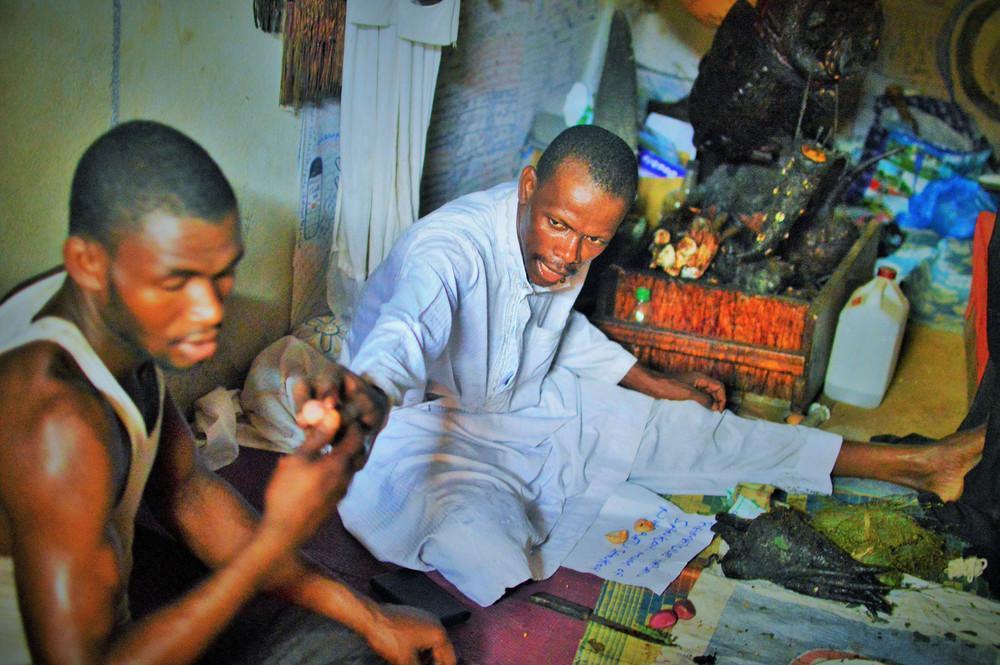 Ο Dr Tarawallie και ο βοηθός του, κατά την διάρκεια της τελετής για να θεραπεύσουν ένα παράλυτο κορίτσι.